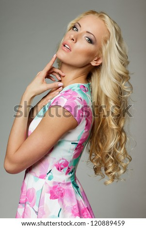 Woman with beauty long blond hair posing at studio, over gray background - stock photo