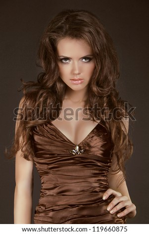 Woman with beauty long brown hair, model posing in elegant dress