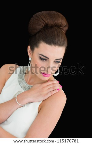 Woman with beehive and pink lips posing on black background - stock photo