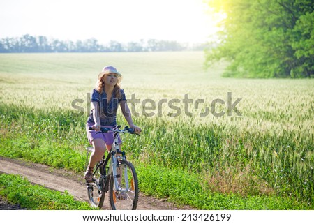 woman with bicycle countryside in summer - stock photo