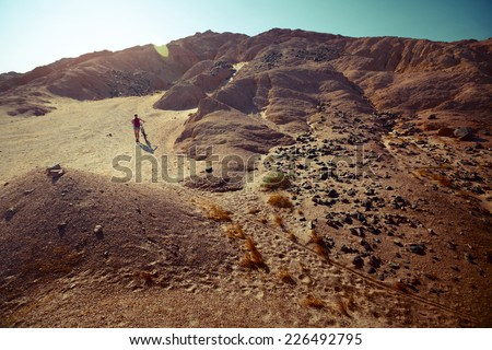 Woman with bicycle crossing desert with rocks - stock photo