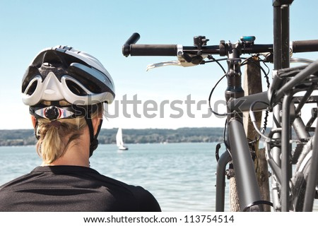 woman with bicycle sits on bank of a lake