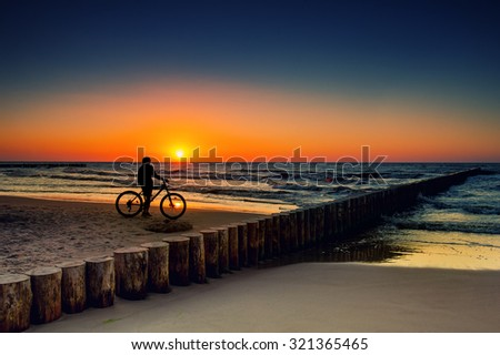 Woman with bicycles on the Baltic Sea at sunset