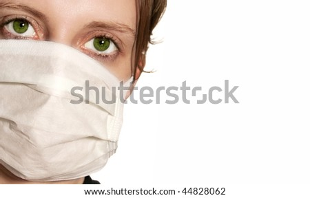 Woman with big green eyes wearing medical mask protecting against flu virus