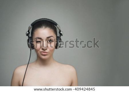 Woman with big headphones and listening to music on a grey background - stock photo