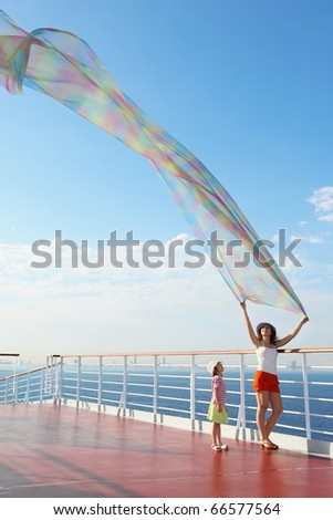 woman with big kerchief standing on deck of cruise ship. little girl looking at kerchief - stock photo