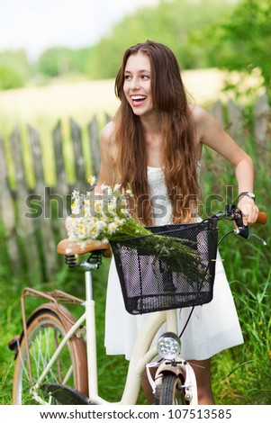 Woman with bike by wooden fence - stock photo