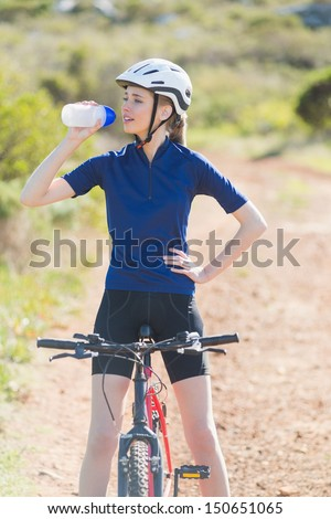 Woman with bike drinking water after biking in the countryside - stock photo