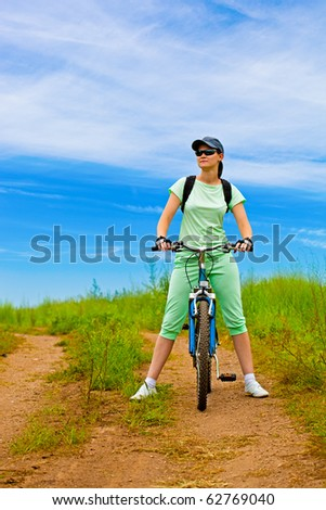 woman with bike on green field under blue skies - stock photo