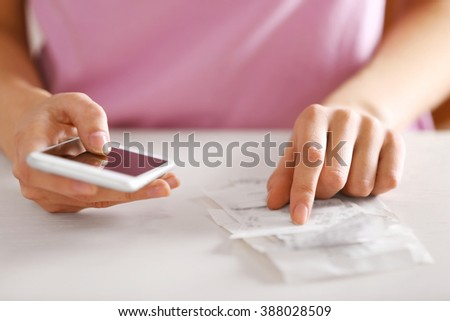 Woman with bills and smart phone at the table. Calculation of costs - stock photo