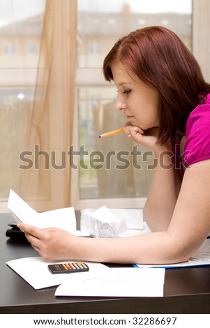 Woman with bills on sofa - stock photo