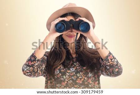 Woman with binoculars over ocher background - stock photo