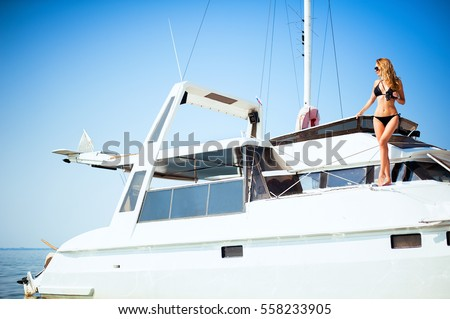 Woman with binoculars standing on a big white yacht with a mast in the sea
