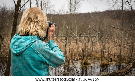 Woman with binoculars viewing Canadian goose in marsh