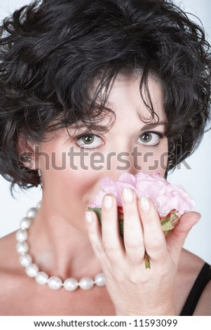 Woman with black curly hair smelling a pink peony flower, in her mid 30s early 40s