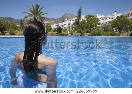 woman with black goggles ready to swim in a blue pool - stock photo