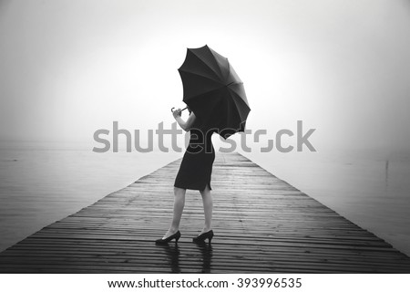 woman with black umbrella looking infinity in a surreal place - stock photo
