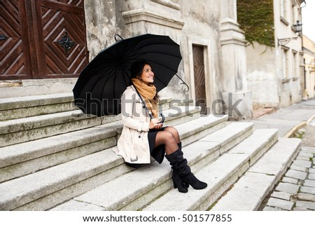 Woman with black umbrella sitting on the stairs in the old town.