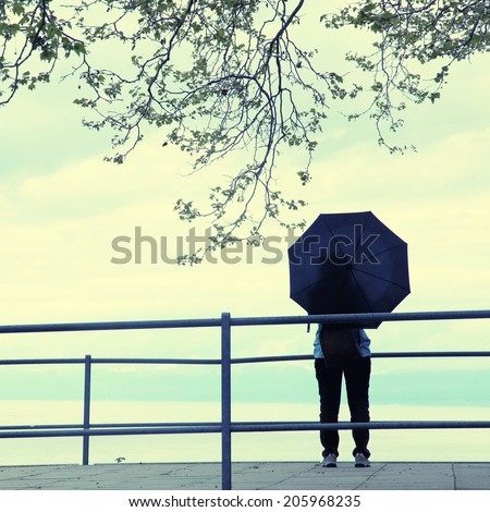 Woman with black umbrella standing on lake pier in rainy day, instagram effect - stock photo