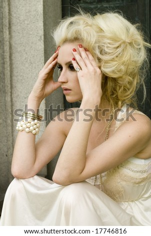 Woman with blonde hair wearing red nail polish and a cream dress - stock photo