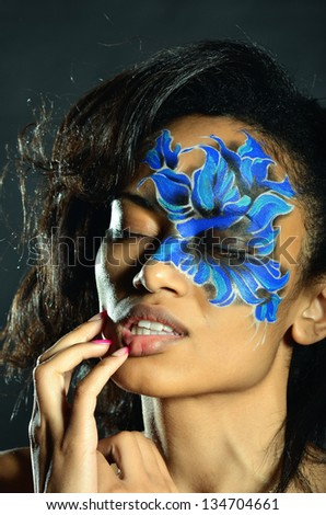 Woman with blue face-art - stock photo