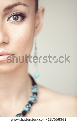 Woman with blue jewelry. Vertical photo - stock photo