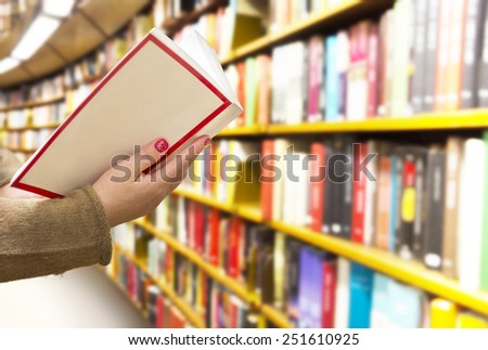 Woman with book in hand in library - stock photo