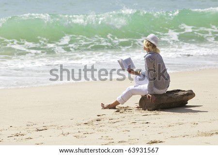 Woman with book is sitting on a stump by the wave line - stock photo