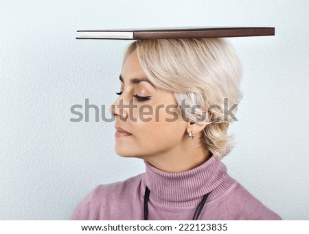 Woman with book on head - stock photo