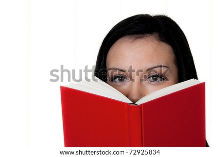 Woman with book reading. Eyes look over the red book.