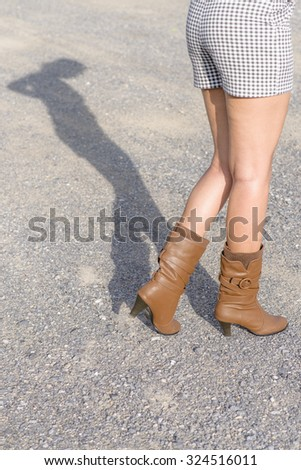 Woman with boot waiting on the road; Shadow shown; High angle shoot - stock photo