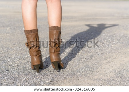 Woman with boot waiting on the road; Shadow shown; Low angle shot - stock photo