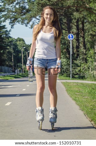 Woman with bottle of water ride rollerblades in the park. - stock photo