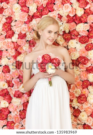woman with bouquet of flowers and background full of roses.
