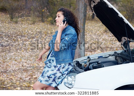Woman with broken car talk on phone with hood up - stock photo