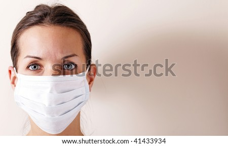woman with brown hair and a medical mask for protection again influenza. Shallow depth of field. Copy space for your text. - stock photo