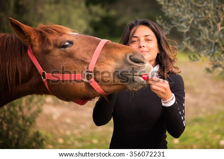Woman with brown hair gives to eat a radish to his horse