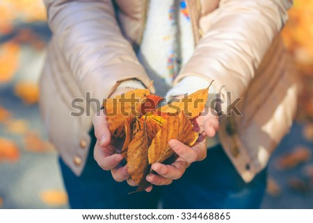 Woman with brown jacket holding golden leaves in hands. Vintage effect.