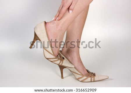 Woman with bruised heel because tight Shoe - stock photo