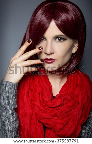 Woman with burgundy red hair and scarf showing nail polish art or manicure design.  The nail art is a stick on design with glitters.   - stock photo