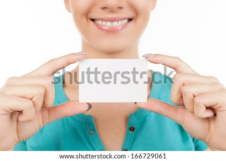 Woman with business card. Cropped image of young woman holding business card in her hand and smiling while standing isolated on white - stock photo