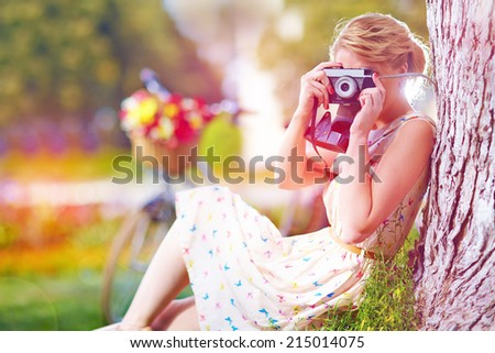 woman with camera relaxing after bicycle ride - stock photo