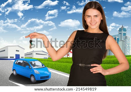 Woman with car key in hand. Small automobile on road - stock photo
