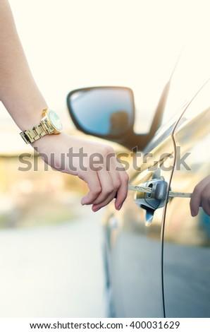 Woman with car key. Opening car door. Woman´s hand unlock a door on a car. Sunlight. Transportation.  - stock photo