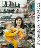 woman with child chooses baby boots at fashionable shop - stock photo