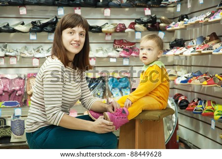 woman with child chooses baby shoes at fashionable shop - stock photo