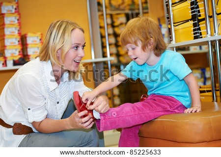 woman with child choosing and trying on new boots in shopping mall - stock photo