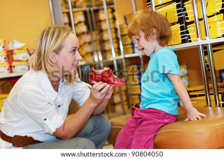 woman with child choosing and trying on new boots in shopping supermarket - stock photo