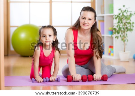 Woman with child doing gymnastics and fitness exercises