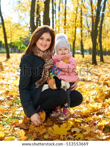 Woman with child girl in autumn city park, happy family